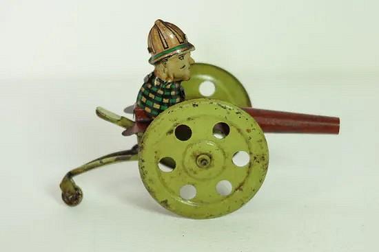 Tin gear driven man on a canon